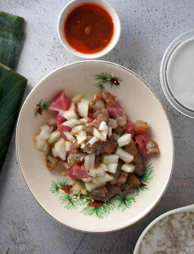 chopped shrimp, pork belly, onions, garlic in a bowl with coconut milk and banana leaves on the side