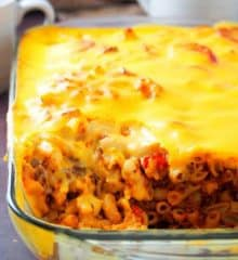baked mac topped with cheese sauce in a glass baking dish