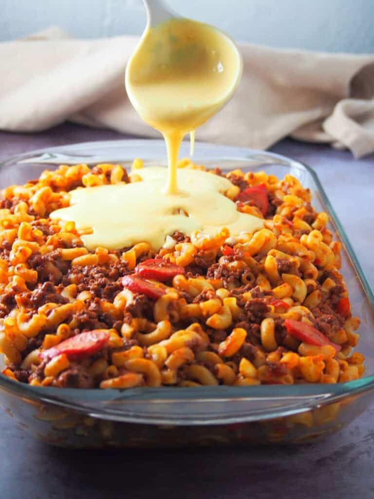 pouring cheese sauce topping on beef macaroni in a baking dish