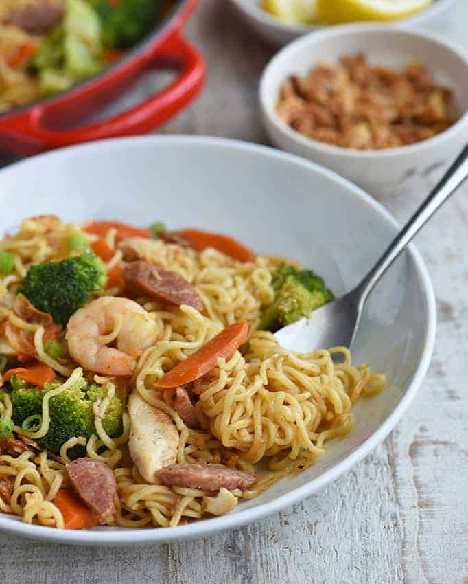 ramen noodle stir-fry with chicken, sausages, shrimp, and vegetables on a white serving plate
