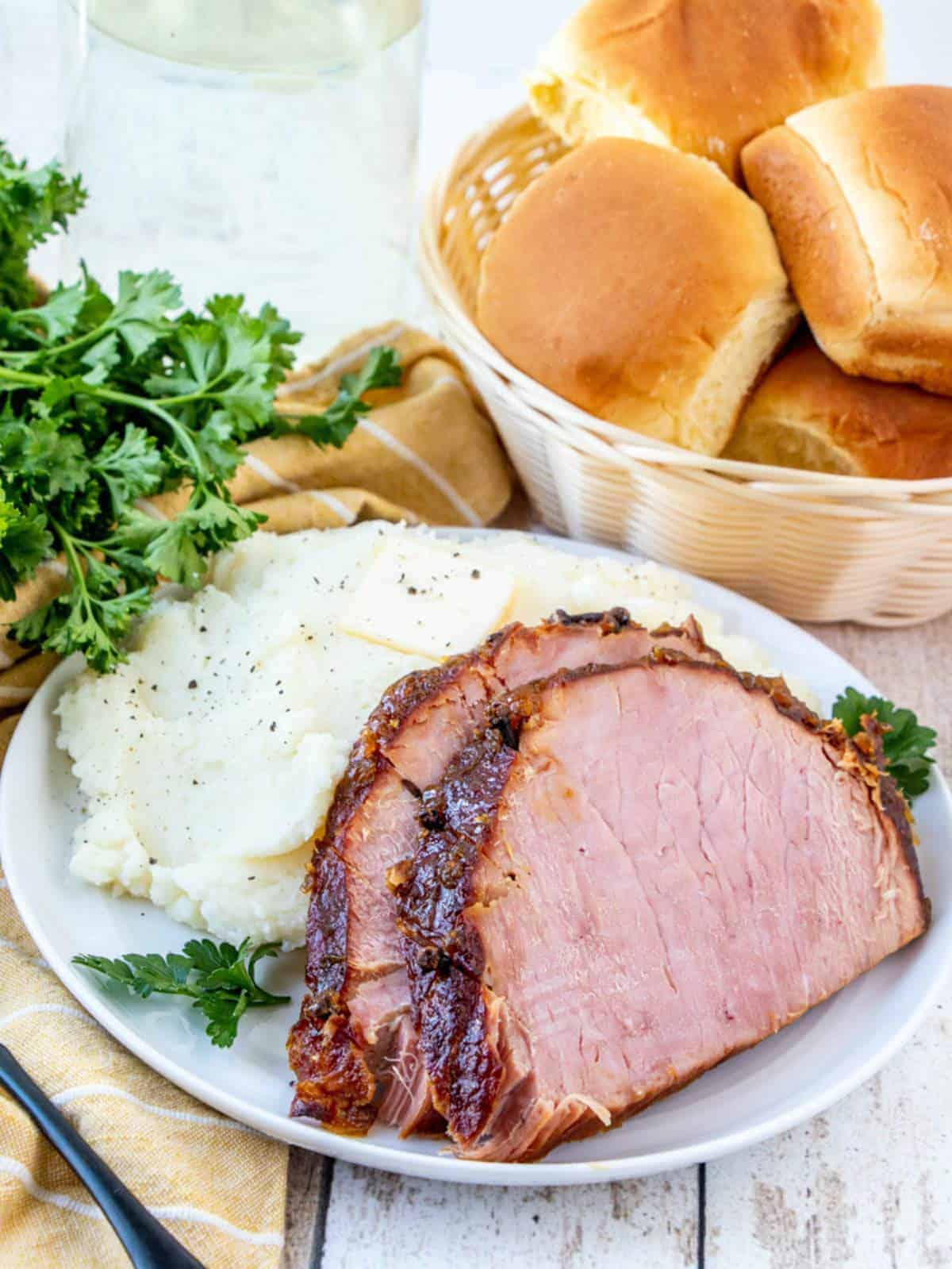 sliced Filipino-style Pineapple Glazed Ham and mashed potatoes on a white plate with a basket of dinner rolls on the side