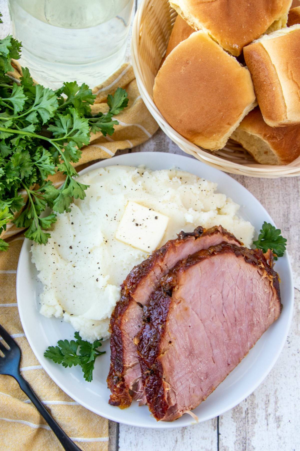 top view of pineapple-glazed ham slices with mashed potatoes on a white plate