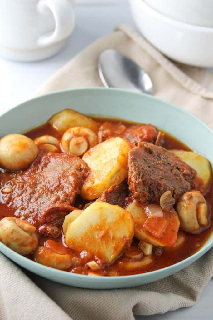 ox tongue stew with mushrooms and potatoes in a blue serving bowl