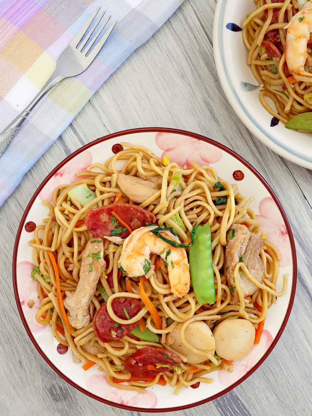 Filipino pancit canton guisado with shrimp, sausage, and veggies on a plate