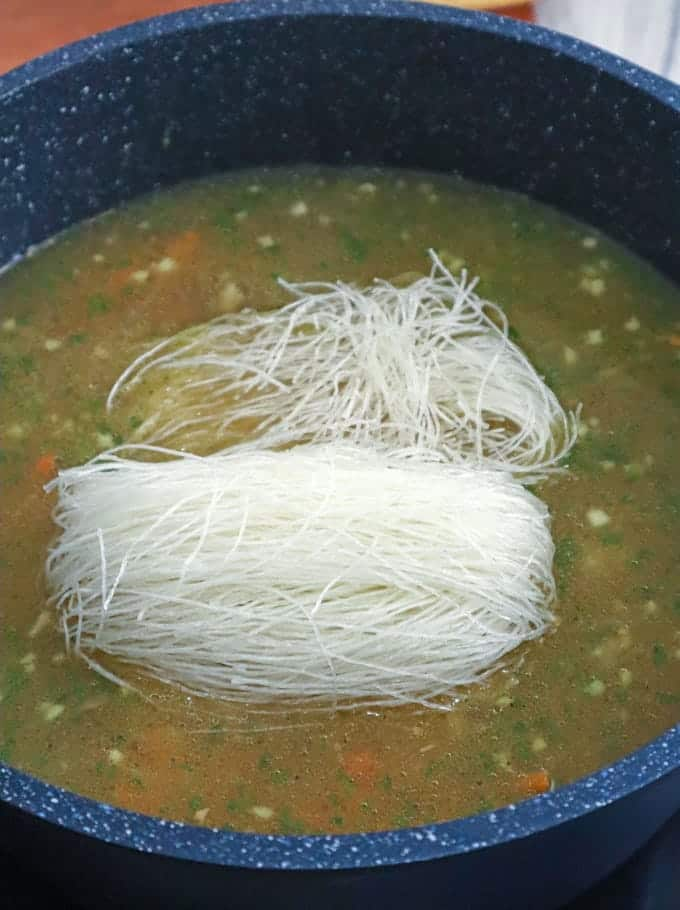 cooking cellophane noodles in broth in a pot