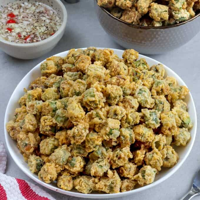 breaded fried okra in a white bowl with spicy vinegar dipping sauce on the side