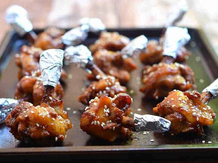 These chicken lollipops are coated in sauce and resting on a baking sheet.