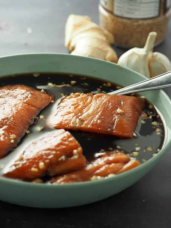 salmon fillets marinating in teriyaki sauce in a light blue bowl