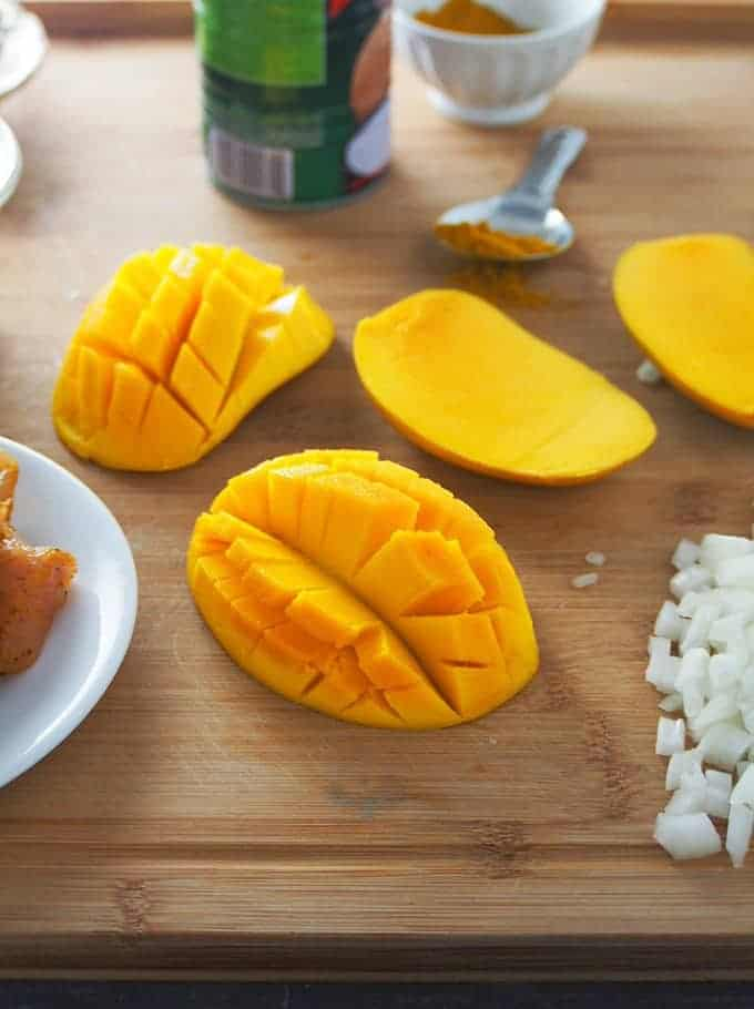 cut up fresh mangoes, chopped onions on a cutting board