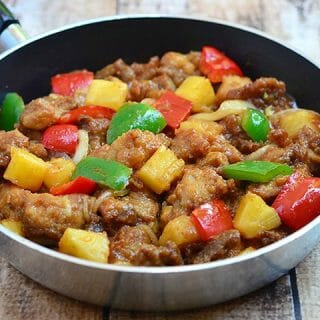 sweet and sour pork with red and green bell peppers and pineapple chunks in a skillet