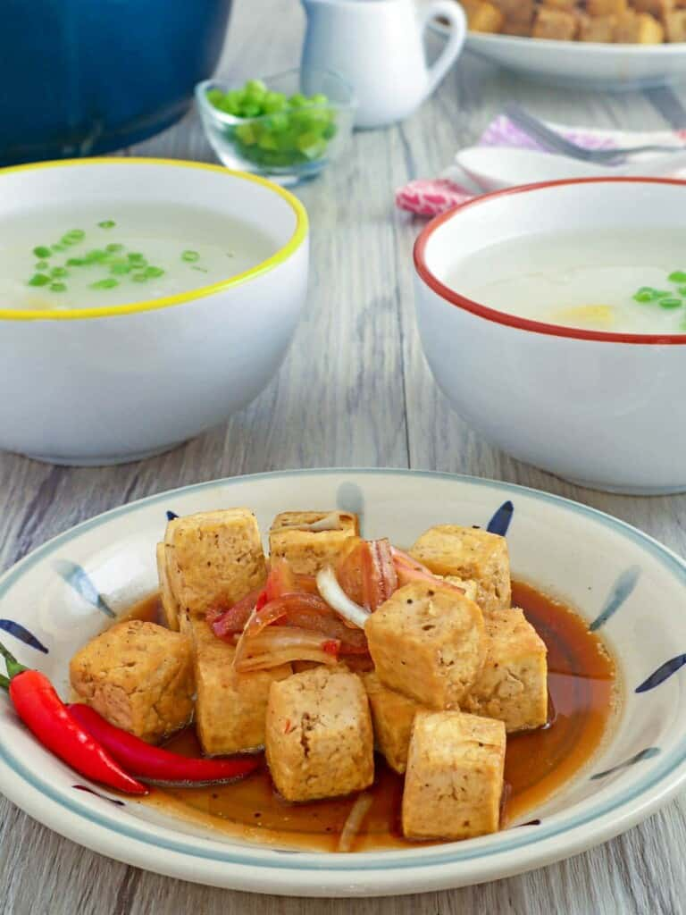 deep-fried tofu with soy sauce-vinegar dressing with a bowl of congee on the side