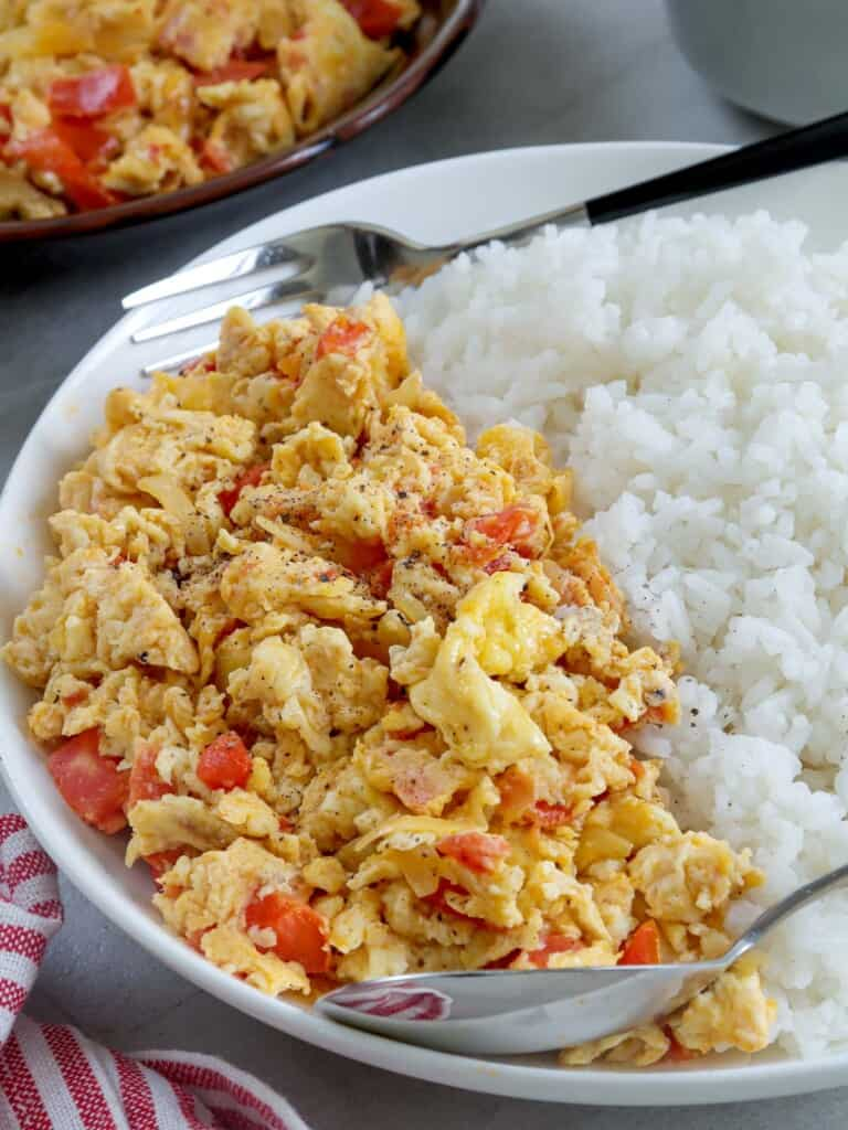 scrambled eggs with tomatoes and onions on a white serving plate with steamed rice