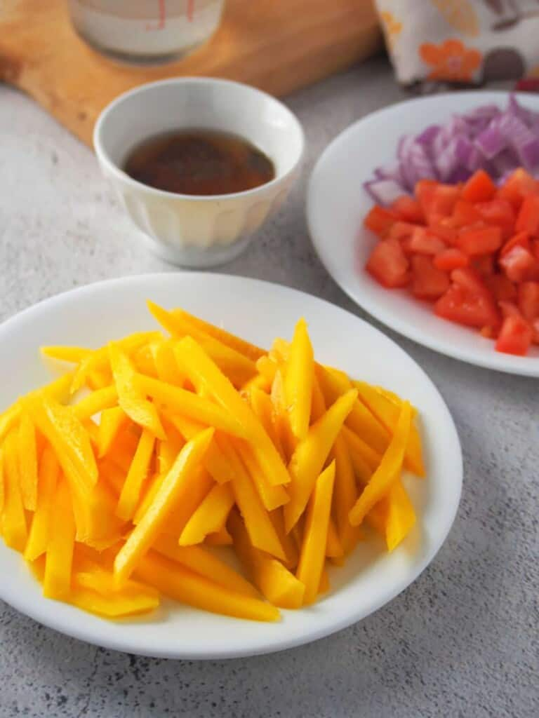 julienned mangoes, chopped tomatoes, chopped red onions, fish sauce, vinegar