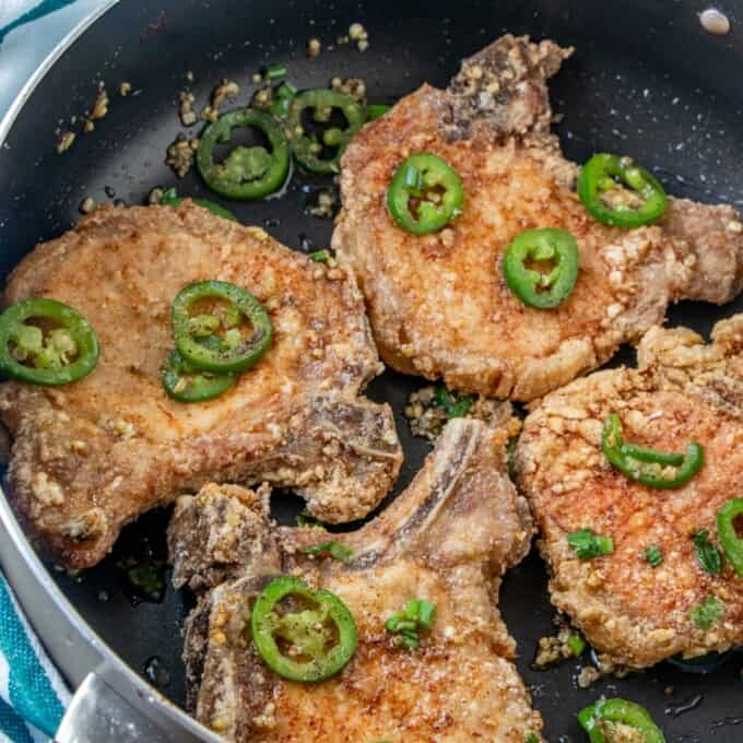 salt and pepper pork chops with sliced jalapenos and browned garlic in a wide pan