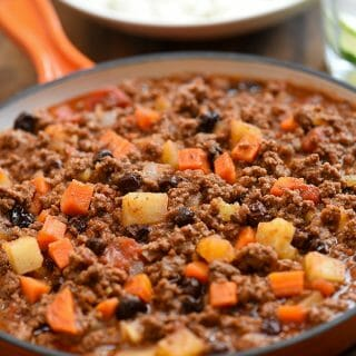 picadillo with potatoes, carrots, raisins, and thick tomato sauce in a orange skillet