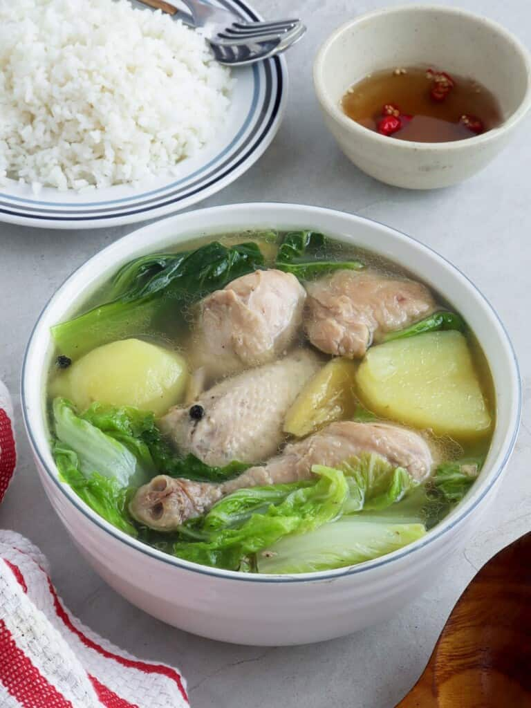 Pesang Manok in a serving bowl with a side of steamed rice and fish sauce
