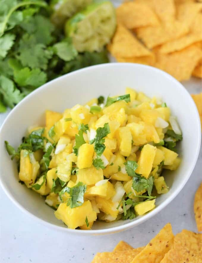 Pineapple Salsa in a white bowl with chips on the side