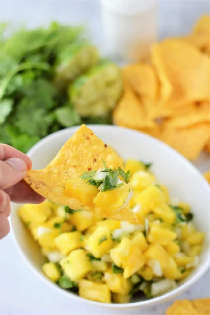 dipping chips in pineapple salsa