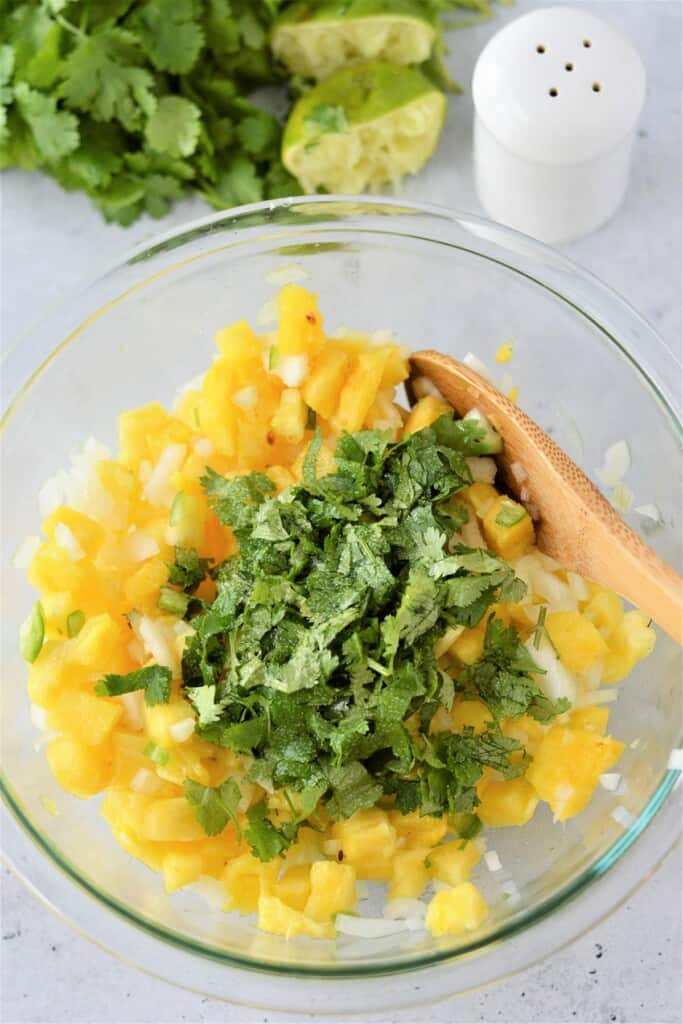 mixing diced pineapples, chopped onions, and chopped cilantro