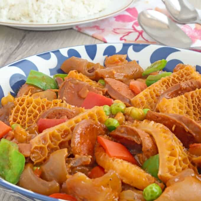 ox tripe stew with garbanzo beans, green peas, and bell peppers in a blue serving bowl