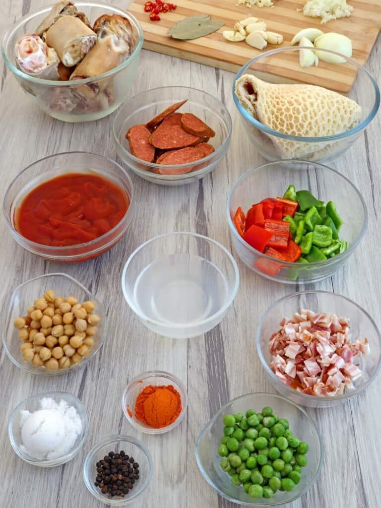 beef tripe, ox feet, chopped bacon, bell peppers, garbanzo beans, paprika, green peas, Chorizo de Bilbao in individual bowls