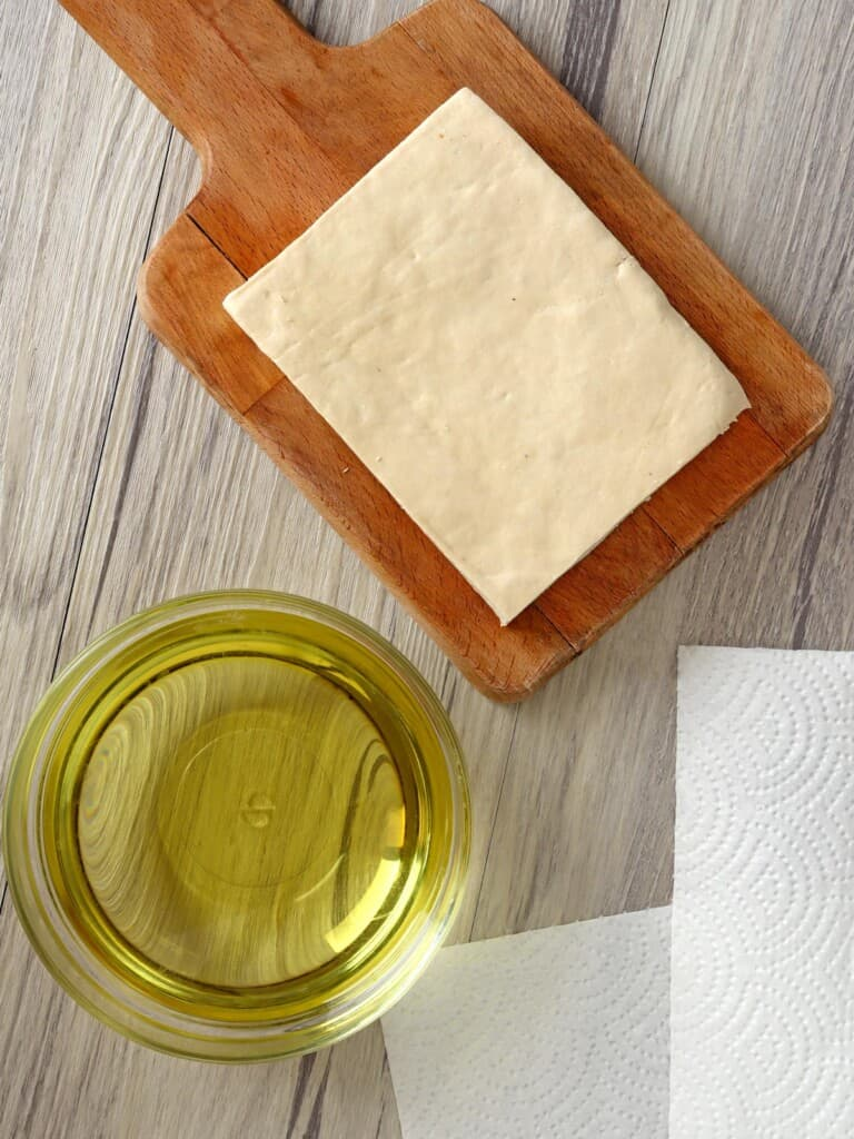 firm tofu block on a cutting board and a bowl of oil