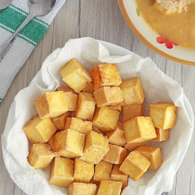 crispy tofu cubes in paper lined bowl