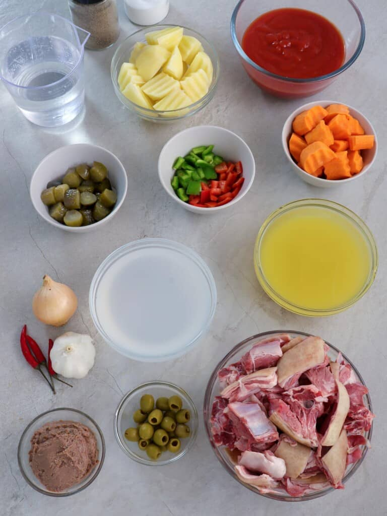 goat meat, vinegar, pineapple juice, gherkins, green olives, bell peppers, tomato sauce, cheese, carrots, potatoes, tomato sauce, liver spread in bowls