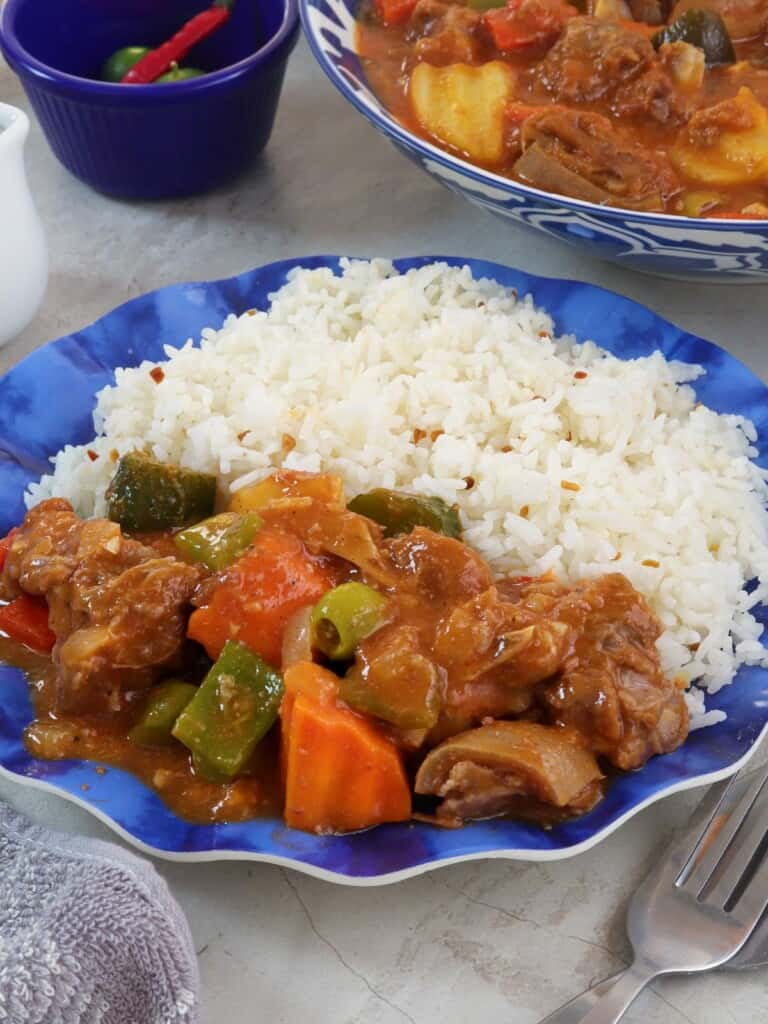 kambing caldereta with steamed rice on a blue plate