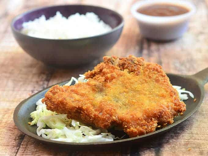 This crispy pork chop is served over a bed of cabbage with rice on the side.