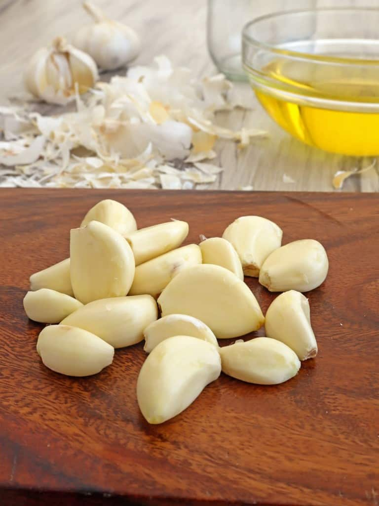peeled garlic on a cutting board and a bowl of canola oil on the side