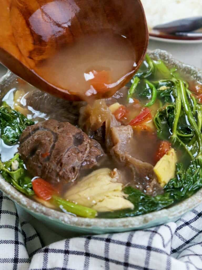 pouring broth on a bowl of beef sinigang with guavas