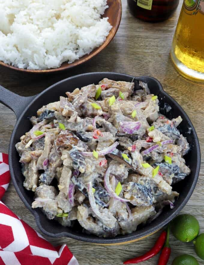 Dinakdakan in a cast iron skillet with a bowl of steamed rice on the side and a glass of beer