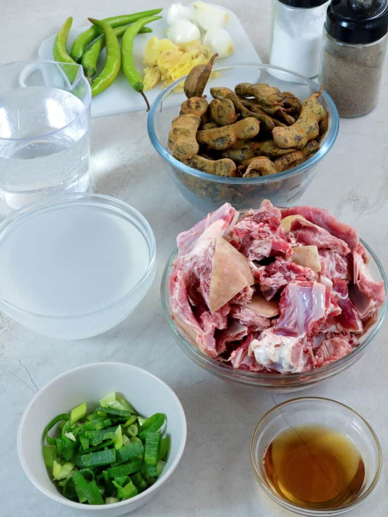 cut goat meat, green tamarind, chili peppers, vinegar, fish sauce, and green onions in bowls