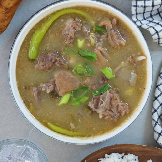 Sinampalukang Kambing in a white serving bowl with a plate of steamed rice on the side