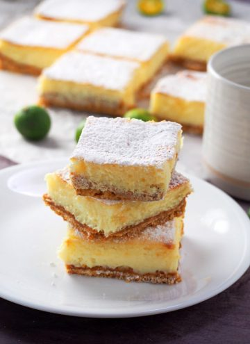 Calamansi Cheesecake Bars stacked on a white plate