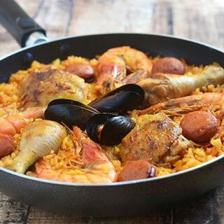 Paella made with saffron-infused rice, chicken, sausage, and seafood is hearty, delicious, and a guaranteed holiday favorite.  This Spanish-style rice dish is easy to make and cooks in one pan!