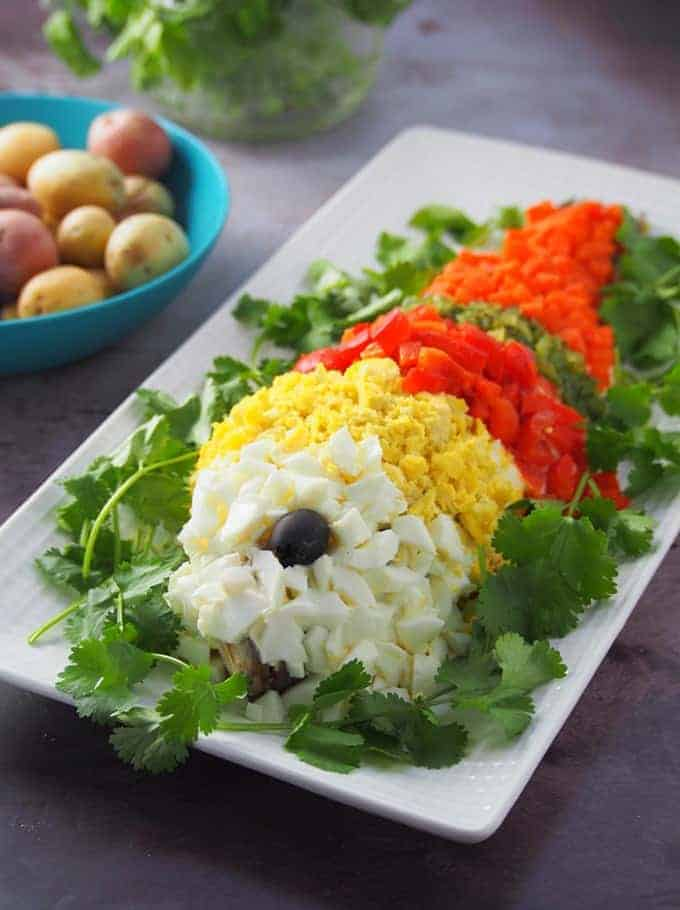 pescao en mayonesa or steamed fishdecorated with chopped eggs, roasted bell peppers, sweet relish, and carrots