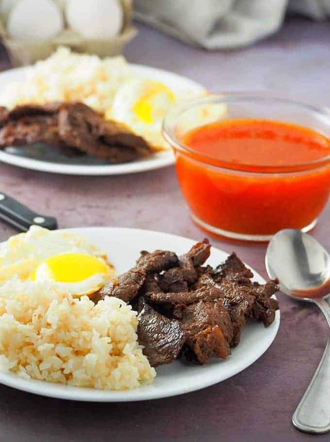 Filipino Beef Tapa with garlic fried rice and sunny side up eggs on serving plates