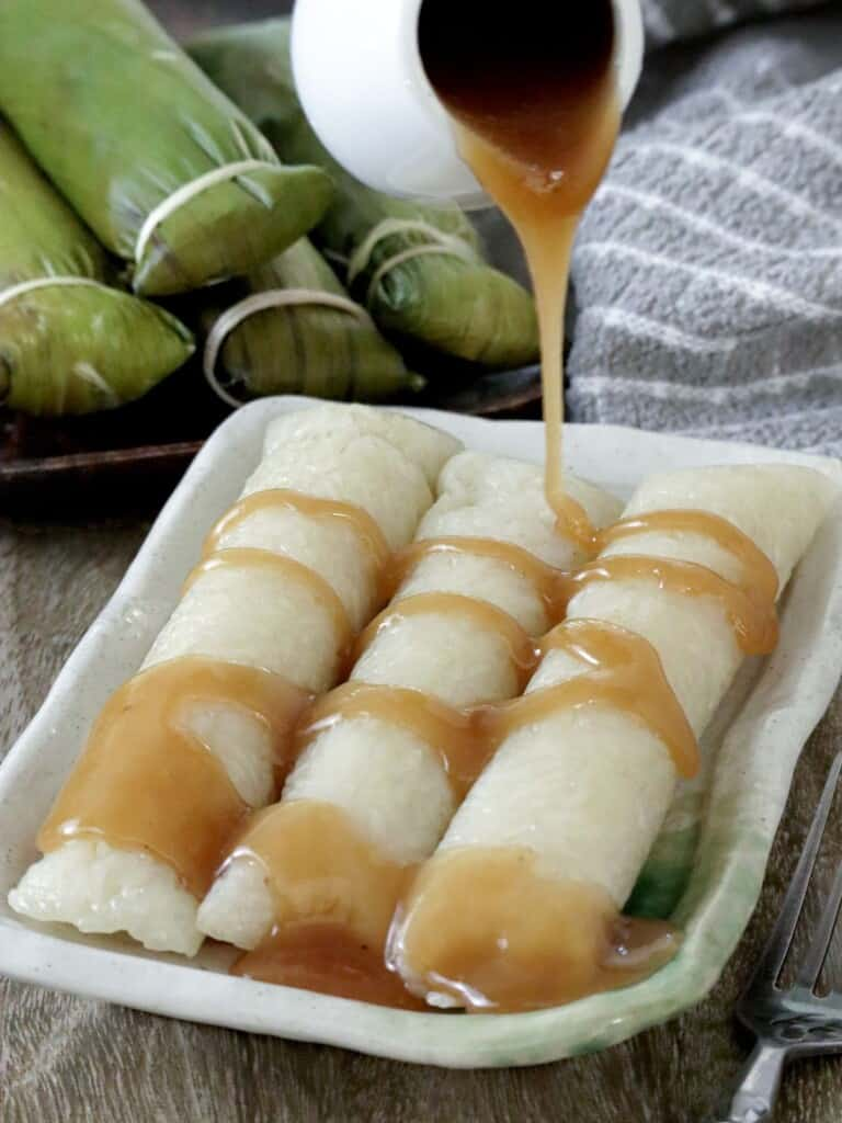 suman malagkit drizzled with coconut caramel sauce on a serving plate