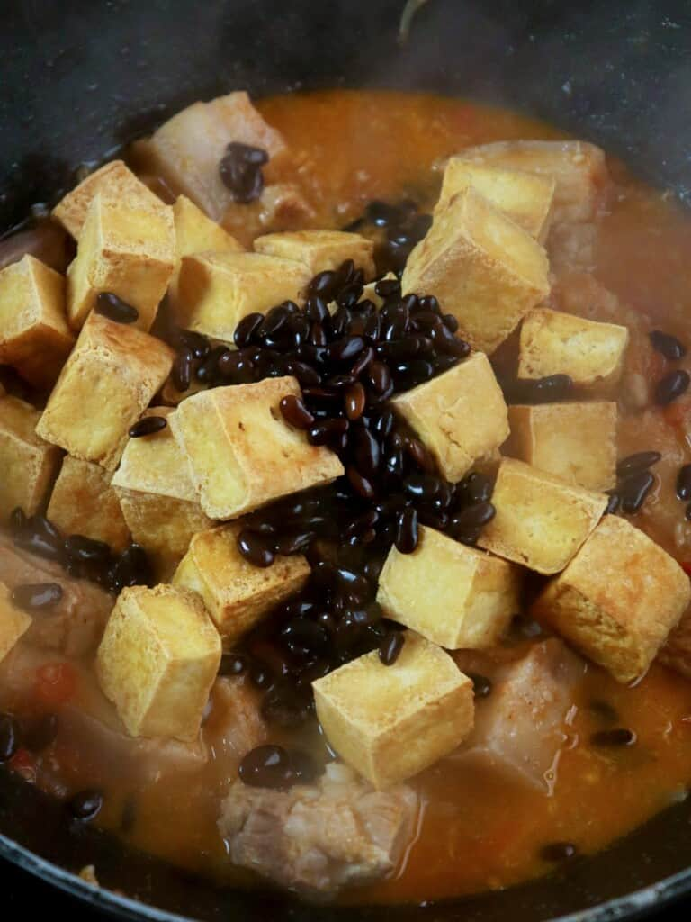 cooking pork and tofu with tomatoes and salted black beans in a pan