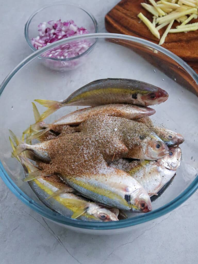 seasoning yellowtail scad with tamarind powder in a clear bowl