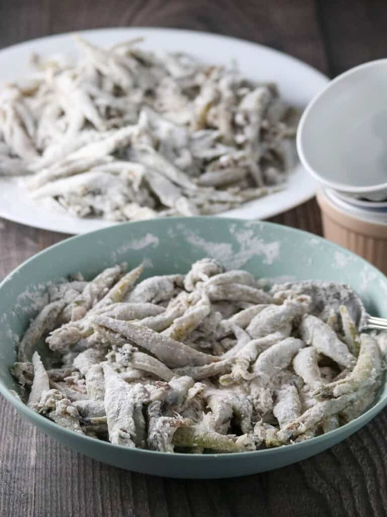 smelt fish coated in cornstarch and flour mixture in a bowl