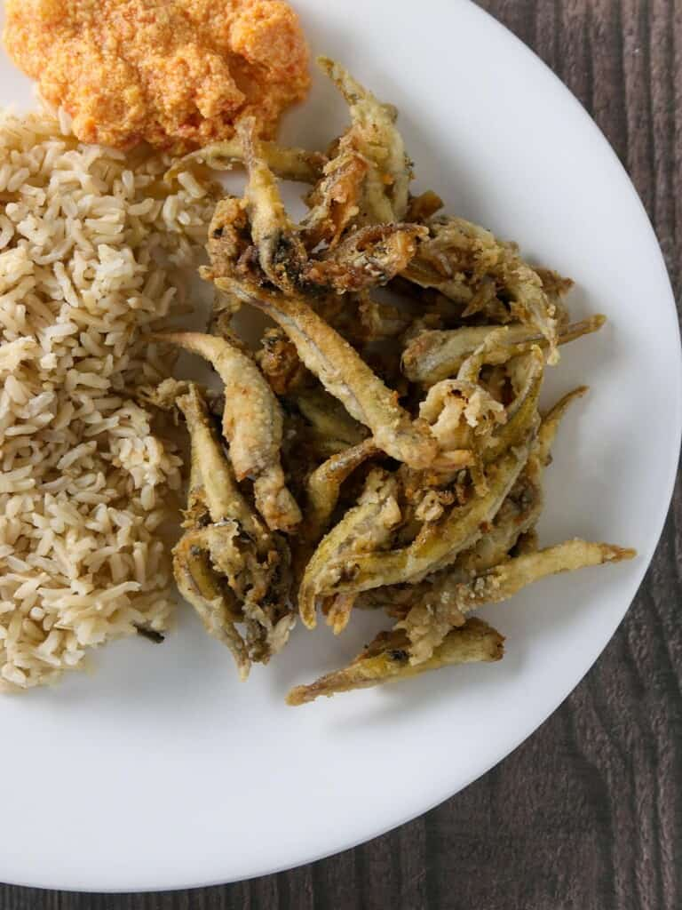crispy smelt fish and brown rice on a white plate