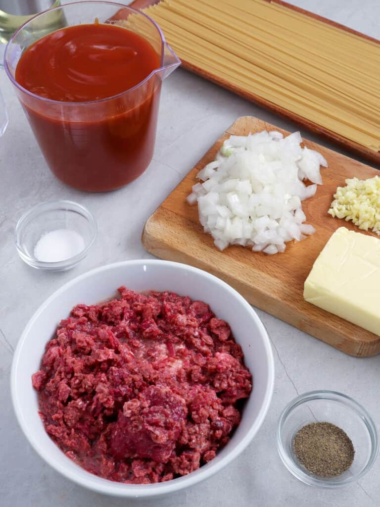 canned corned beef, spaghetti sauce, spaghetti noodles, chopped onions, and minced garlic