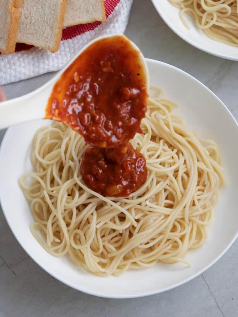 ladling meat sauce on a plate of spaghetti