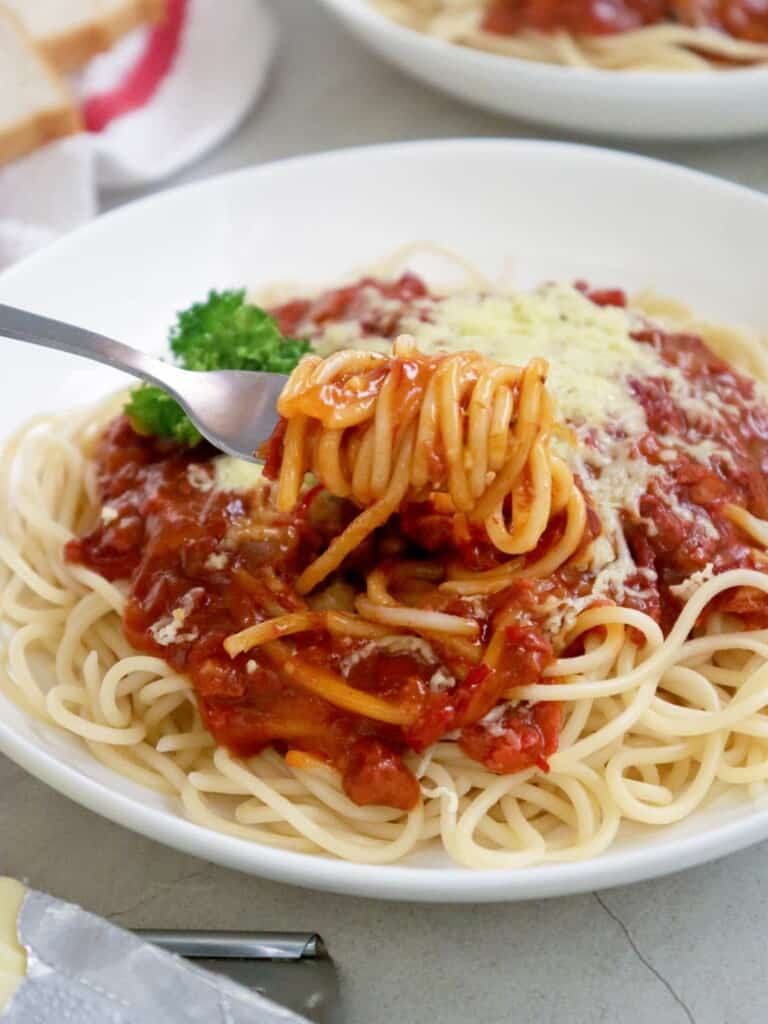 eating Corned Beef Spaghetti on a white serving plate with a fork