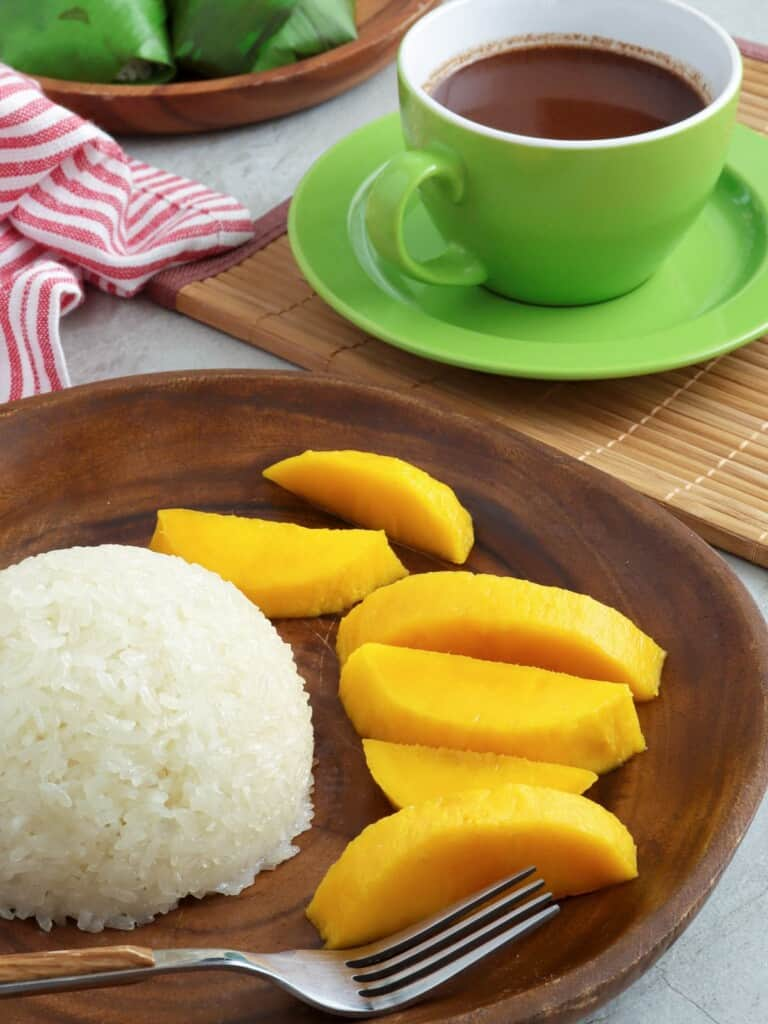 puto maya, sliced mangoes on a wooden plate with a cup of hot chocolate on the side