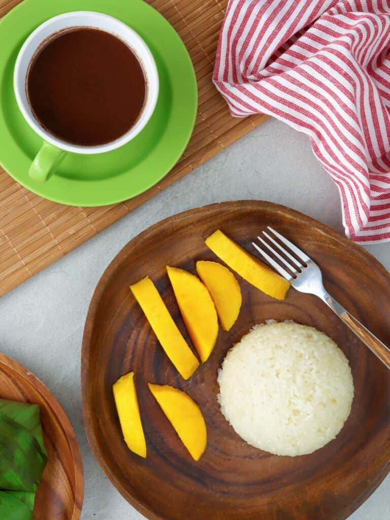 puto maya with sliced mangoes on a wooden plate and a cup of sikwate