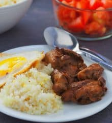 Chicken Tapa with garlic fried rice and sunny side up eggs on a white plate with a bowl of chopped tomatoes on the side